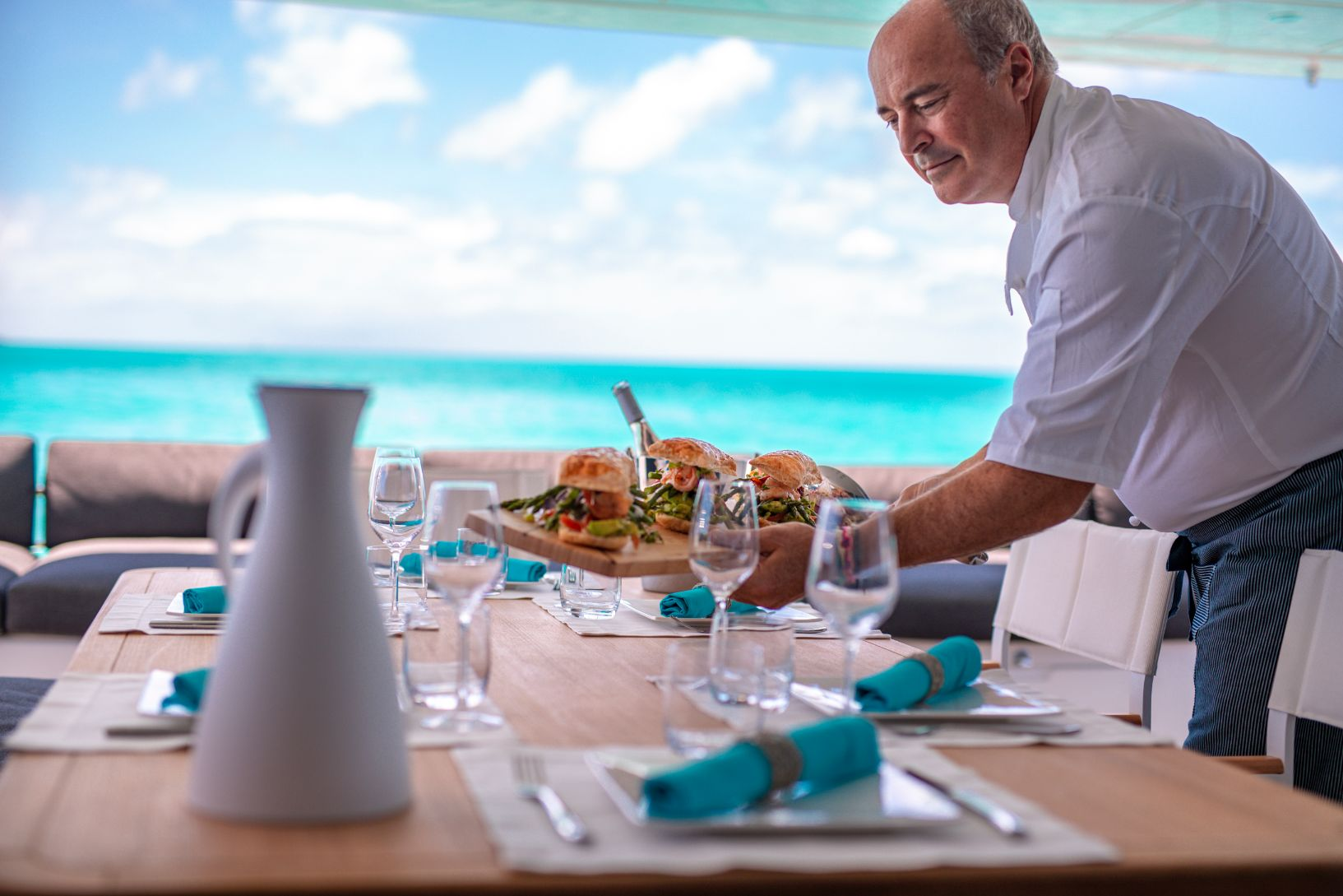 Chef servant un plateau de sandwich gastronomiques sur catamaran aux bahamas