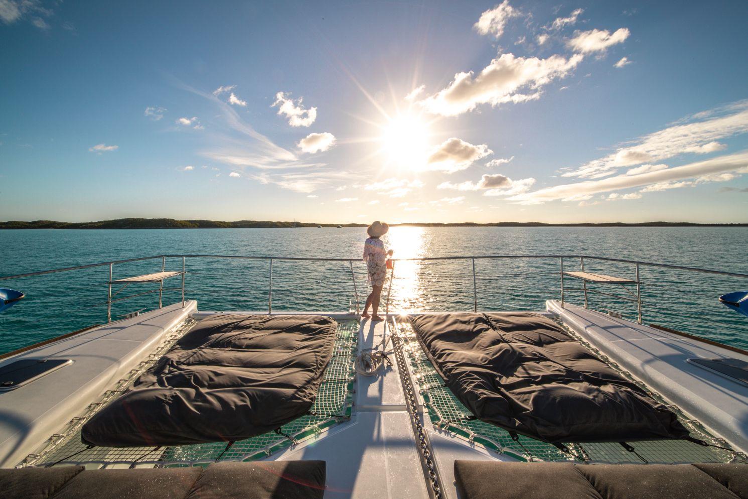 Femme admirant le coucher de soleil à l'avant du catamaran