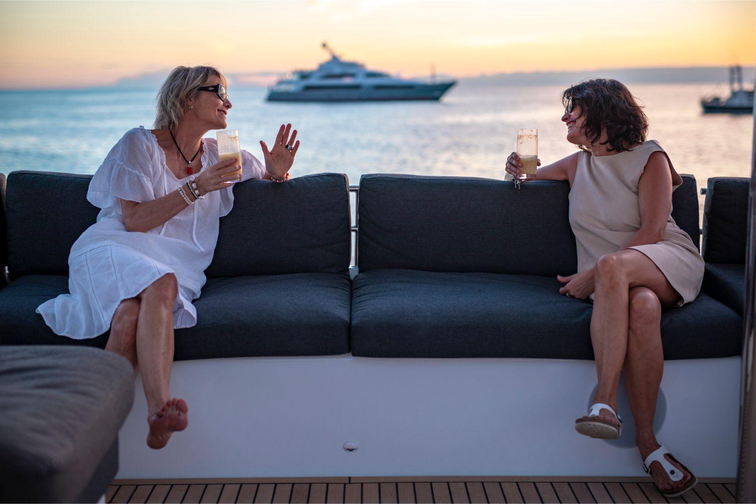 Femmes prenant un verre sur banquettes du catamaran   Bateau de Marc Saulnier   Serenity Navigation
