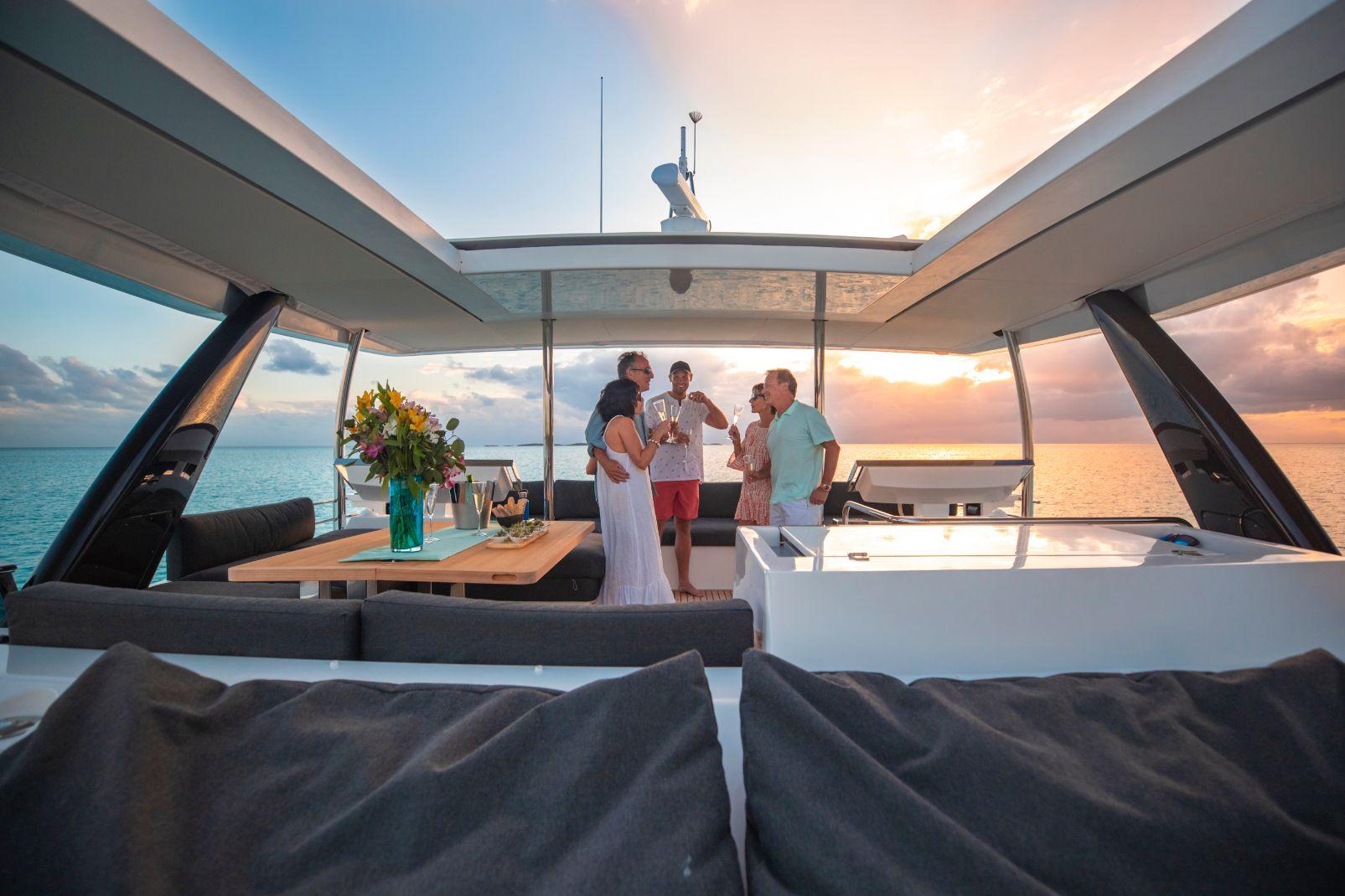 Amis discutant sur l'étage supérieur catamaran à moteur bahamas   Bateau de Marc Saulnier   Serenity Navigation